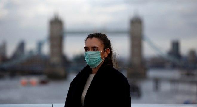 Mulher usa máscara contra o coronavírus em frente à Ponte de Londres