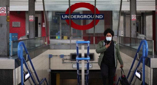 Mulher sai de estação de metrô em Londres usando máscara: serviço essencial