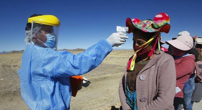 Membros de uma comunidade quechua em Puno passam por checagem de temperatura
