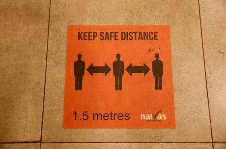 Placas lembram pessoas de manterem distância