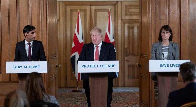 Johnson (c) e Sunak (e) anunciam medidas contra o coronavírus em Londres