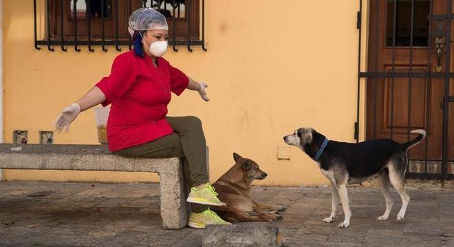 Mulher brinca com cachorros na República Dominicana usando máscara e luvas