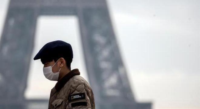 Um turista usa uma máscara de proteção perto da Torre Eiffel, em Paris, França