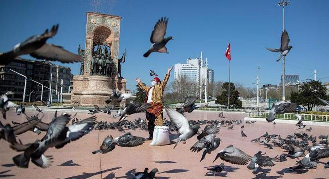 Homem alimenta pombos na maior praça de Istambul, vazia durante a pandemia
