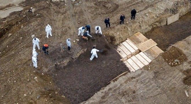 Dezenas de corpos de vítimas da covid-19 são enterrados em vala comum em Nova York