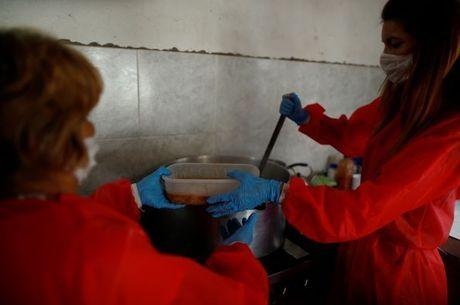 Voluntários com máscaras servem comida