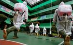 Voluntários da Cruz Vermelha da Indonésia se preparam para pulverizar desinfetante em uma escola fechada em meio à disseminação do coronavírus