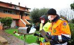 Voluntários do VAB (corpo florestal) para erradicar a propagação da doença por coronavírus entregam uma máscara de porta em porta a todos os habitantes do município de Castiglione della Pescaia, Grosseto, Itália