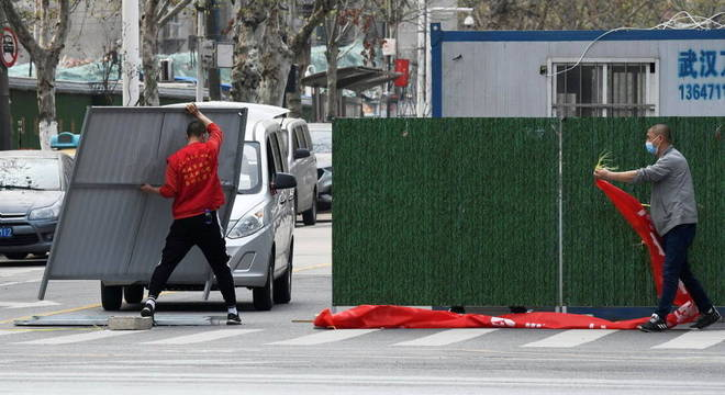 Trabalhadores retiram barreiras em ruas de Wuhan: quarentena será suspensa