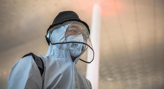 Passageiro com equipamento de proteção em aeroporto de Wuhan