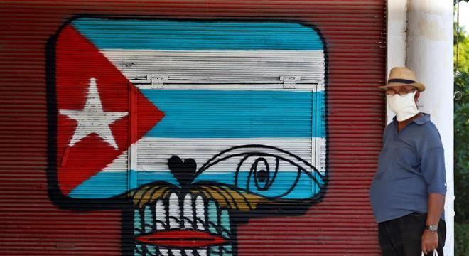 Homem com máscara caminha pelas ruas de Havana, capital de Cuba