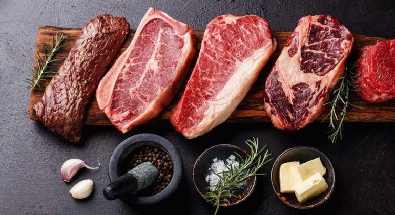 Cortes de carne bovina sobre uma tábua de madeira com temperos ao lado, como alho, pimenta do reino, alecrim e manteiga