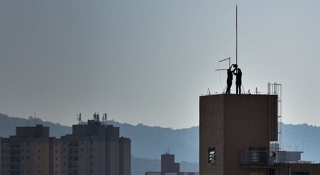 Homens trabalham em para-raios no alto de um prédio na zona norte de SP