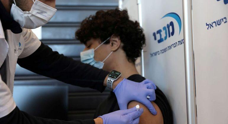 Adolescente recebe vacina contra a covid-19 em Israel neste domingo (24)