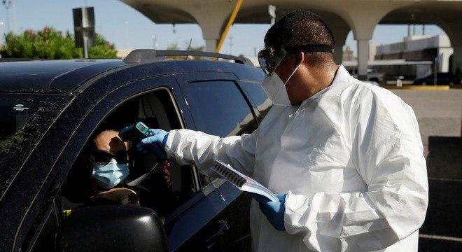 Paramédico mede temperatura de viajante chegando dos EUA ao México