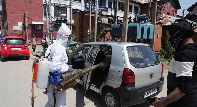 Funcionário aplica spray desinfetante em carro para combater a pandemia