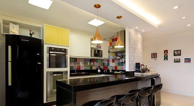 Cozinha americana com azulejos coloridos e geladeira preta