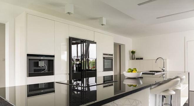 Cozinha americana com bancada extensa e geladeira preta duas portas