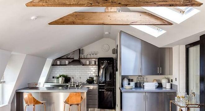 Cozinha americana em inox com geladeira preta