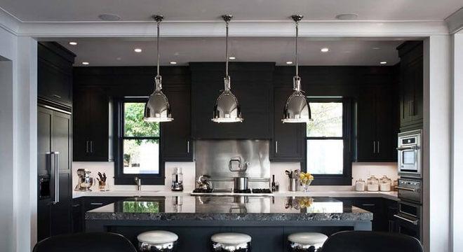 Cozinha com bancada central e geladeira preta side by side