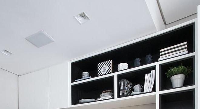 Cozinha compacta com diversos nichos e geladeira preta