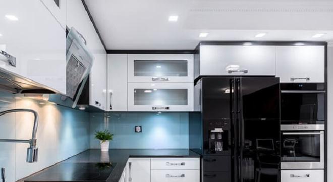 Cozinha em formato l com geladeira preta side by side