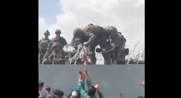 Homem ergue um bebê e um soldado puxa pelo braço para passar por cima do muro do aeroporto
