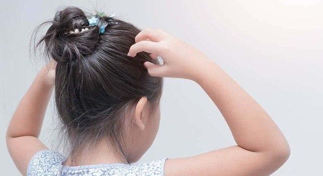 criança com piolho coceira na cabeça