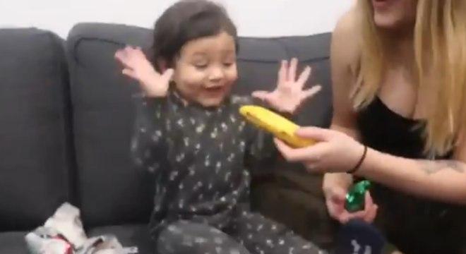 A criança comemorou após abrir o embrulho e descobrir que era uma banana