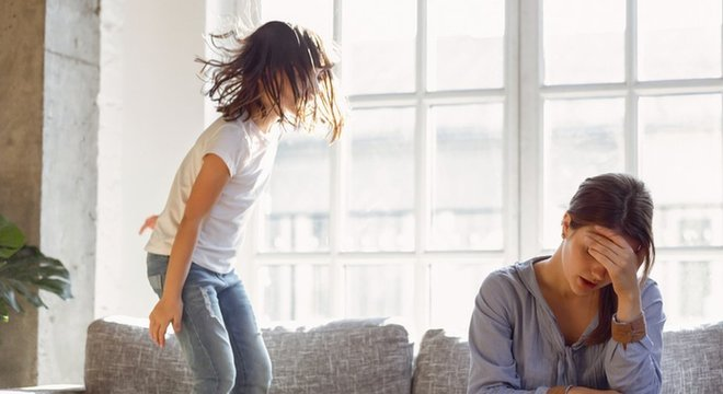 Criança pulando no sofá