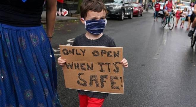 """Criança segura cartaz que diz: """"abrir somente quando for seguro"""""""