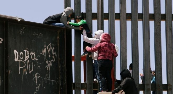Criança sendo levada pela fronteira; número de migrantes detidos está no maior nível desde 2006, mas mesmo assim está distante do pico dos anos 2000