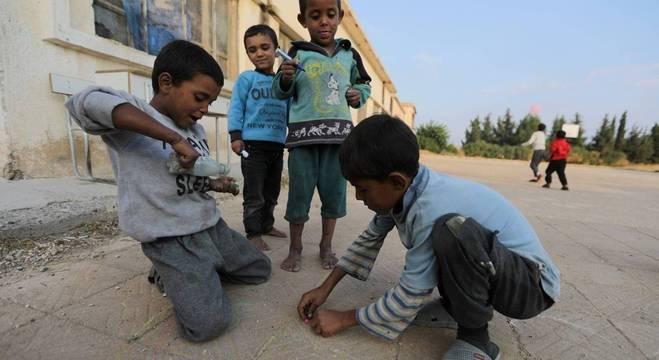 Crianças brincam na Síria em meio as péssimas condições de vida