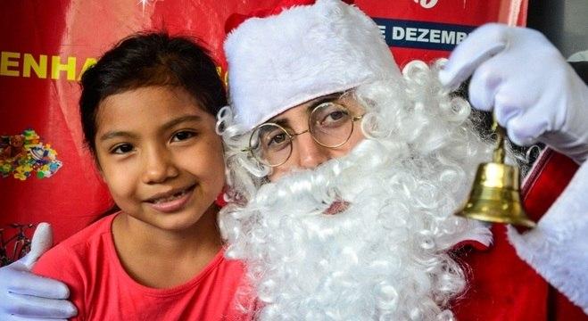 Criança recebe presente do Papai Noel em 2019, festa deste ano terá uso de máscaras