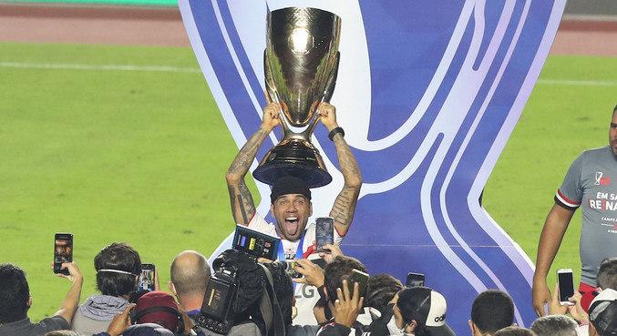 Daniel Alves levanta a taça do seu 41º título. É o jogador mais vencedor de todos os tempos