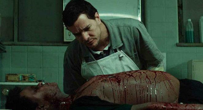 Stênio (Daniel de Oliveira) conversa com cadáver no IML, em 'Morto Não Fala'