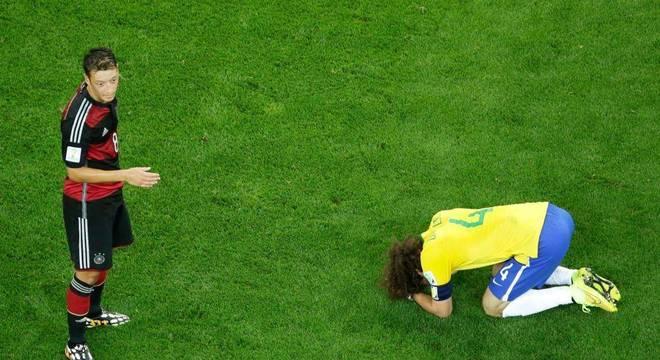 David Luiz aos pés de Ozil após o vexame no Mineirão. Retrato do fracasso