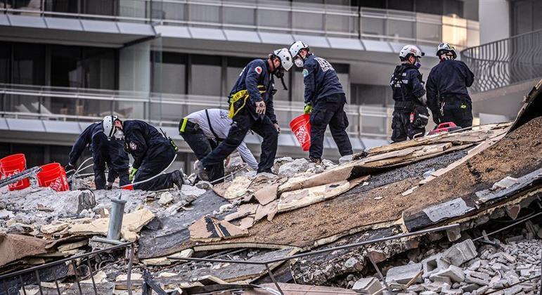 Equipes trabalham na busca por vítimas sob os escombros do prédio que desabou na quinta-feira (24)