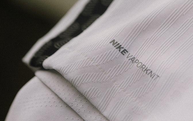Detalhe da lista vertical lateral na cor preta e as informações do tecido fornecido pela Nike.
