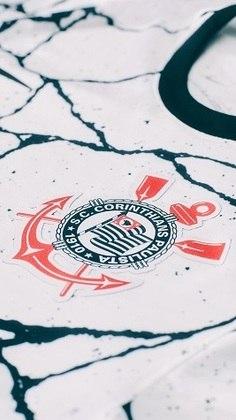 Detalhe do símbolo do clube no lado esquerdo do peito em meio às linhas imperfeitas em preto.