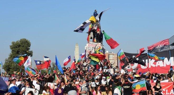 Dezenas de pessoas com bandeiras e cartazes em área aberta no Chile, algumas em cima de estátua
