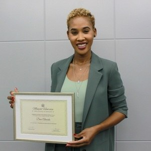 A jornalista Dina Almeida e o prêmio recebido