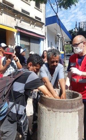 Moradores de rua precisam lavar as mãos antes de receber a marmita