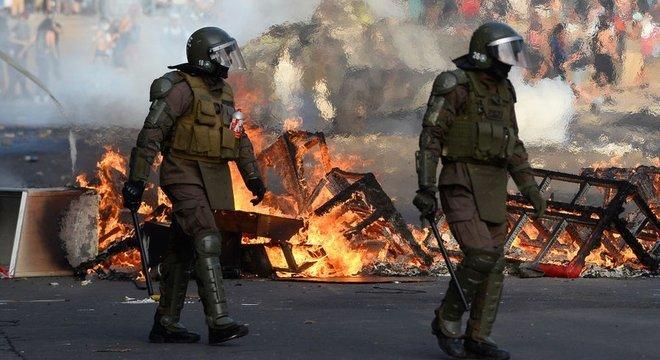 Dois homens fardados e com capacetes andam em meio a objetos em chamas na rua