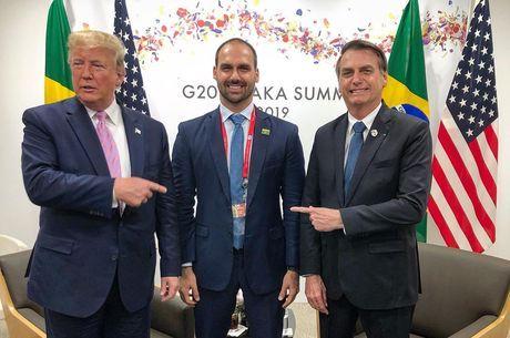 Eduardo Bolsonaro entre o pai e o presidente dos EUA