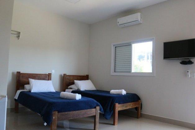 Dormitório com duas camas, ar condicionado e sistema de televisão.