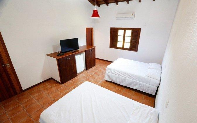 Dormitório do centro de treinamento, com TV e ar condicionado.