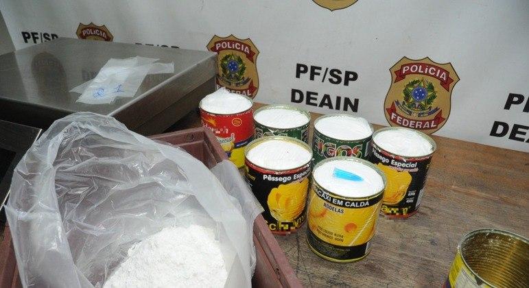 PF apreende drogas dentro de latas de compota de frutas no aeroporto de SP