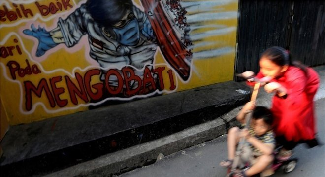 Crianças brincam na Indonésia; isolamento delas, com fechamento de escolas e menor necessidade de ir à rua como adultos, pode explicar papel menor na transmissão