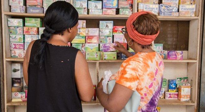 Duas mulheres olham para uma prateleira com produtos de medicina tradicional.